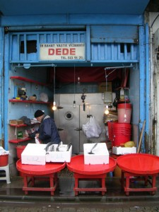 Shop with red tables, a man in a coat and hat, and a sign saying DEDE