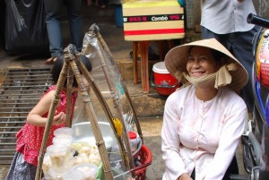 Smiling woman in straw hat and white dress sitting next to food displayed in bamboo frames, watched by playful girl in red dress.
