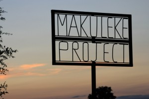 "Wooden sign: ""Makuleke Project"" against a sunrise"