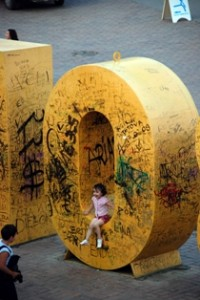A little girl in shorts sitting in a beige, grafitti-covered 0-shaped structure.