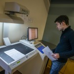 photo of a student at the scanner in Hayden Library
